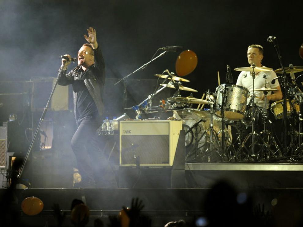 Bono, cantente de U2, con Larry Mullen tras él, durante una actuación en 2009