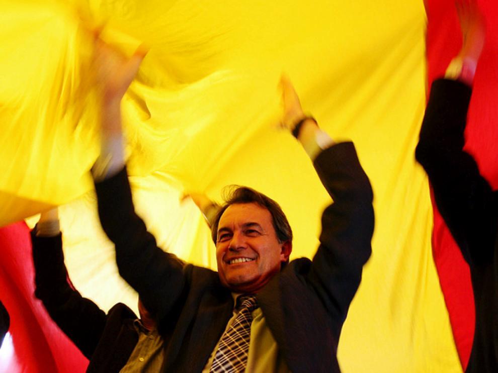 El candidato de CiU, Artur mas, levanta una 'senyera'.