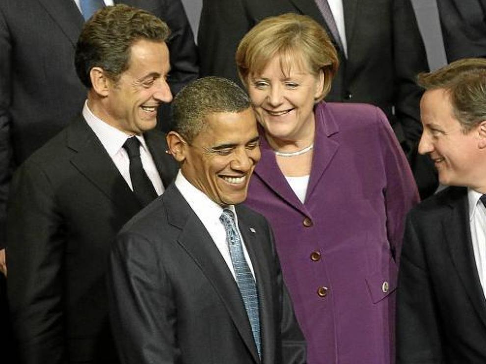 Sarkozy, Obama, Merkel y Cameron sonríen durante la foto de grupo de la cumbre de la OTAN.