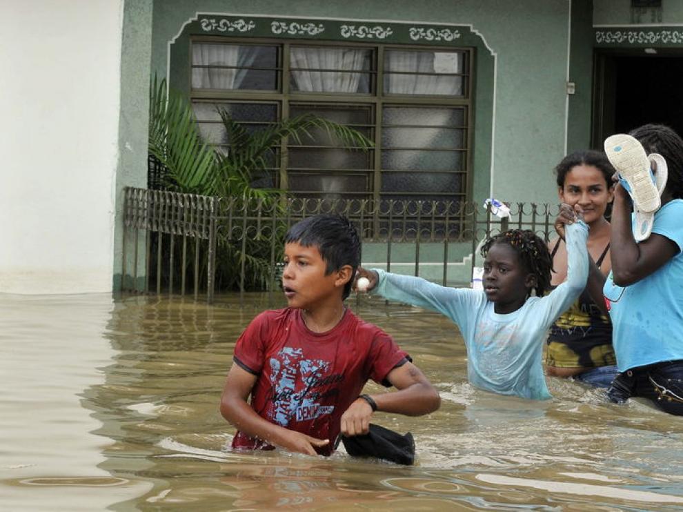 Unos niños intentan cruzar la calle inundada