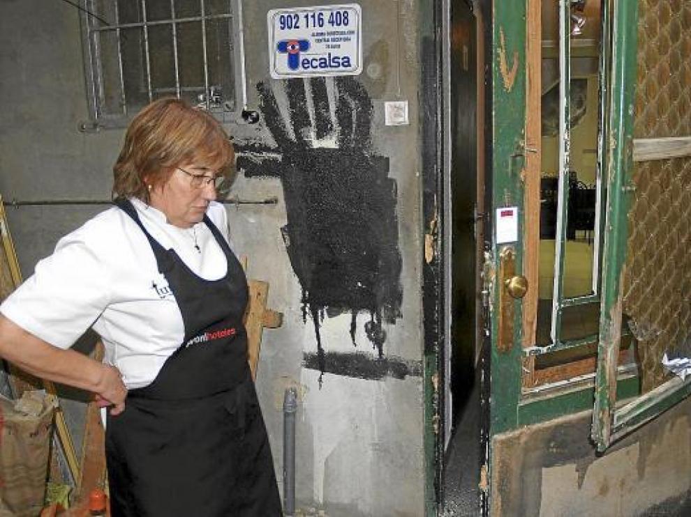Lourdes Escartín, dueña del bar, observa los desperfectos en la puerta forzada por los cacos.