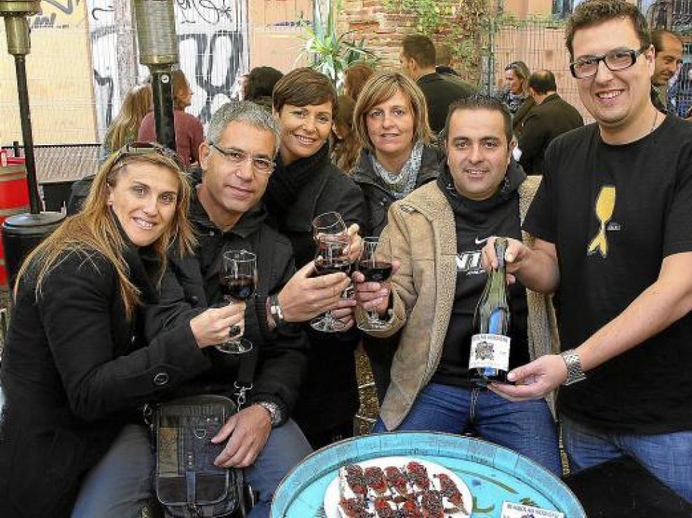 Clientes y el propietario de Bodegas Almau, brindando ayer con vino 'Beaujolais nouveau'.