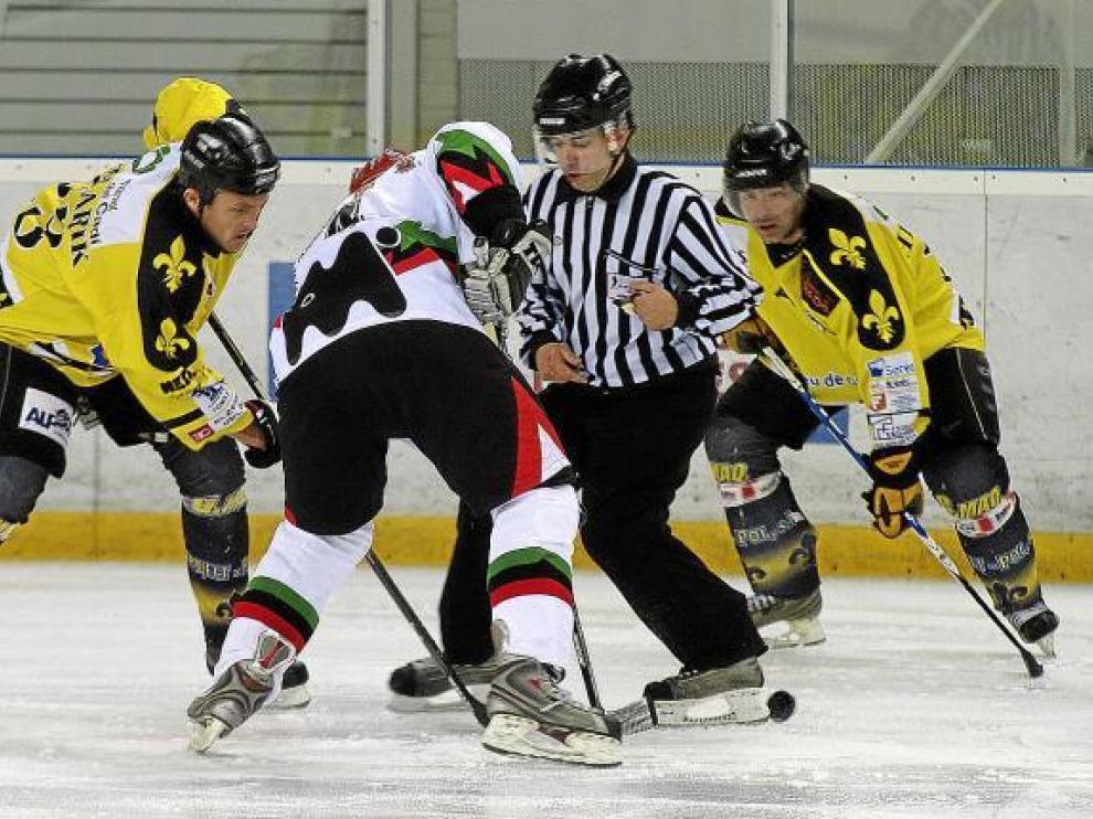 Un jugador del Aramón CH Jaca se lleva la pastilla tras ser puesta sobre le hielo por el árbitro.