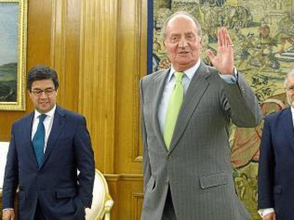 El Rey saluda a la prensa ante el presidente del BID (izda.)