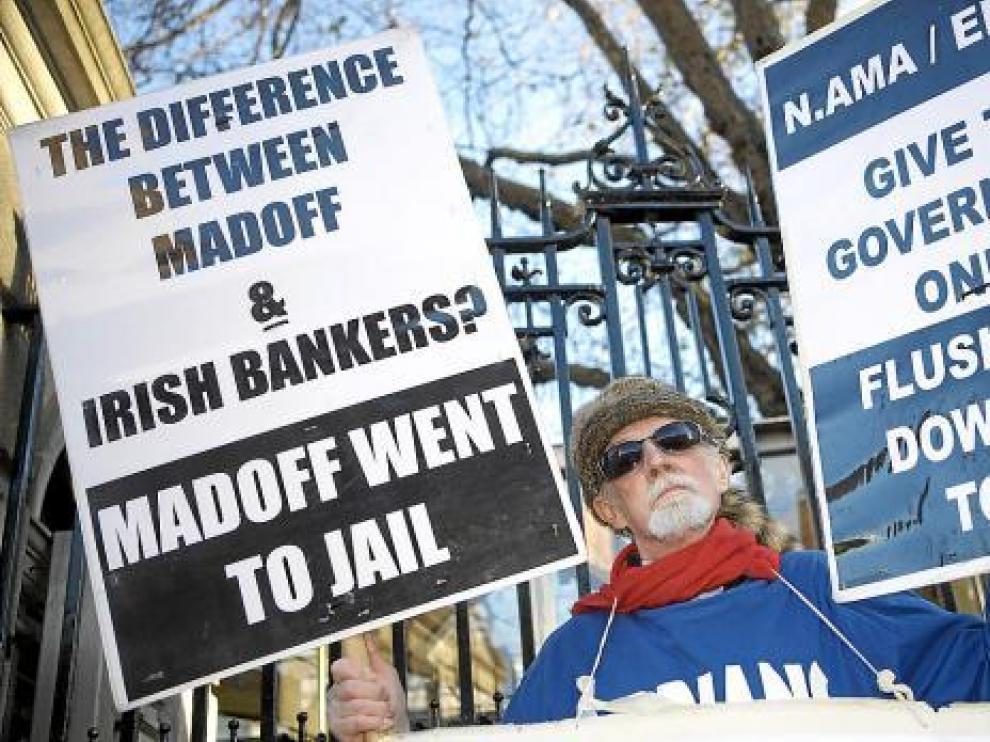 Un hombre protesta con dos pancartas a las puertas del Parlamento irlandés en Dublín.