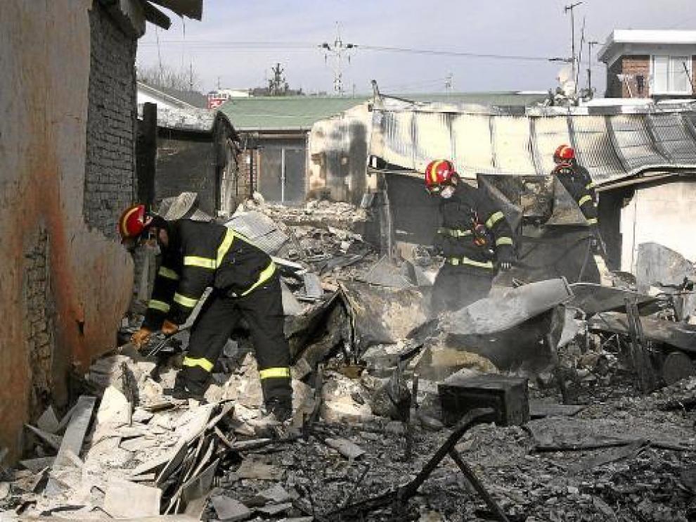 Miembros de emergencia, entre los restos de las casas destruidas, el martes en Yeonpyeong.