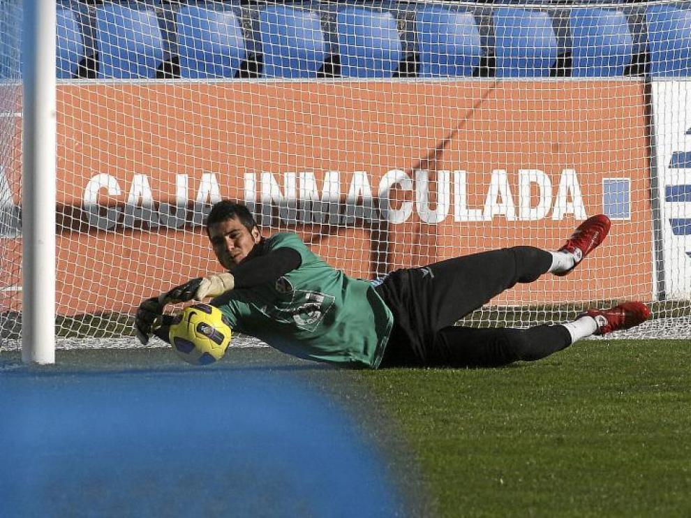 Andrés se estira para atajar un balón durante el entrenamiento que el Huesca hizo, ayer, sobre el césped de El Alcoraz.