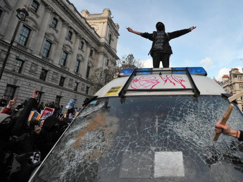 varios manifestantes destrozan un coche de policía.