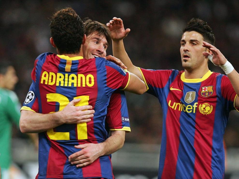 Messi se abraza con Adriano para celebrar uno de los goles del Barça