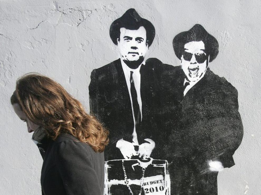 Una irlandesa pasa ante un mural que representa al primer ministro irlandes y al ministro de Finanzas