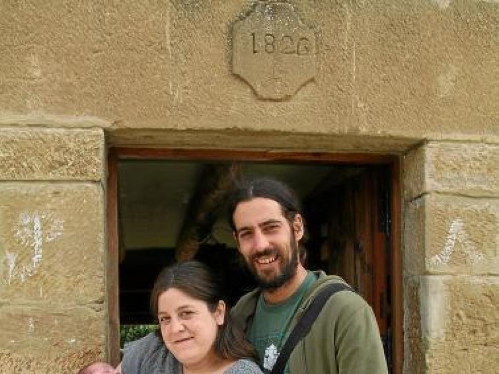 Carlota y Jorge, con el pequeño Diego, junto a su hotel rural.