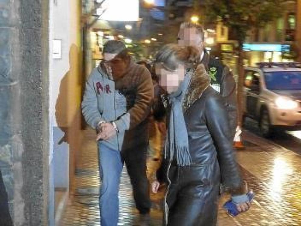 El detenido, esposado, a la entrada del domicilio.