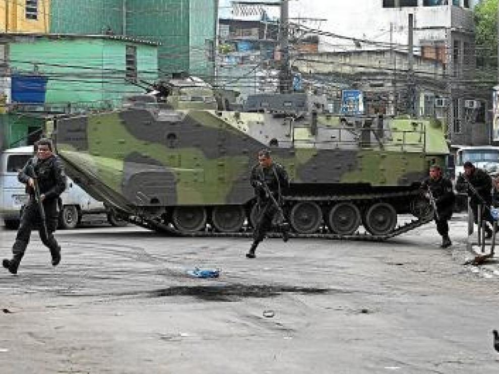Policías desembarcan de un blindado en la favela Vila Cruzeiro.