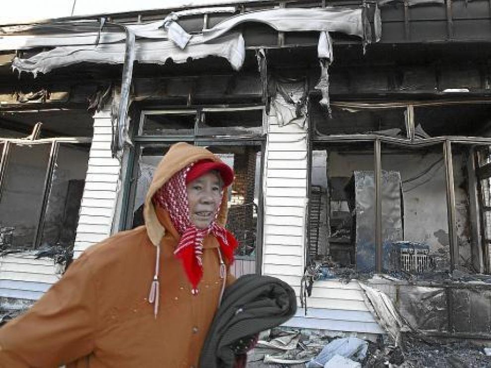 Una mujer pasa junto a una casa destruida en la isla surcoreana de Yeonpyeong, ayer.