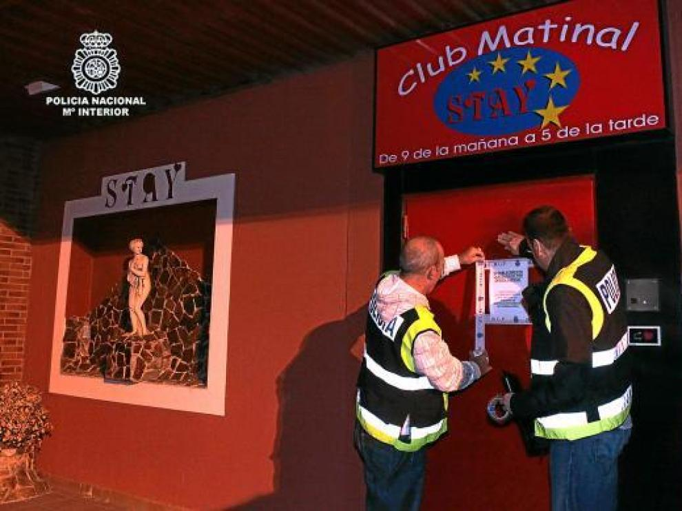 Los agentes colocan la orden de cierre en la puerta del local Stay, de Alagón.
