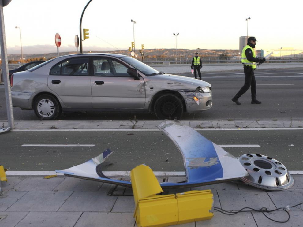 El coche implicado en el accidente, junto a varios objetos de la calzada destrozados