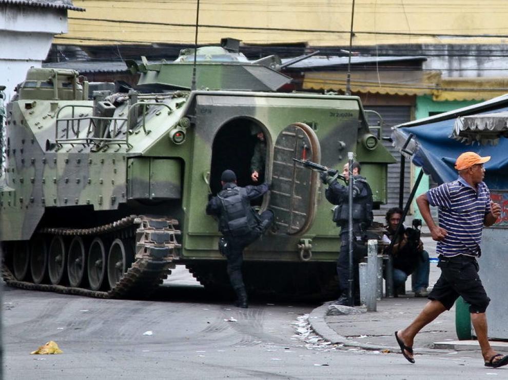 Varios policías prestan guardia junto a un vehículo de las Fuerzas Armadas en una de las zonas conflictivas de Río de Janeiro