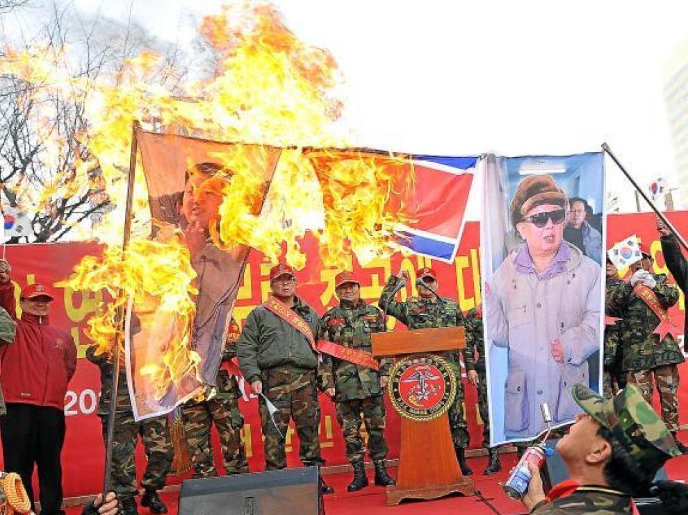 Veteranos militares surcoreanos queman banderas y fotos de los líderes norcoreanos, ayer en Seul.