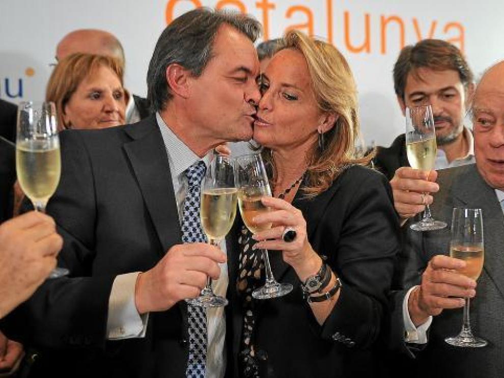 Artur Mas besa a su esposa en presencia de Jordi Pujol en la celebración del triunfo electoral.