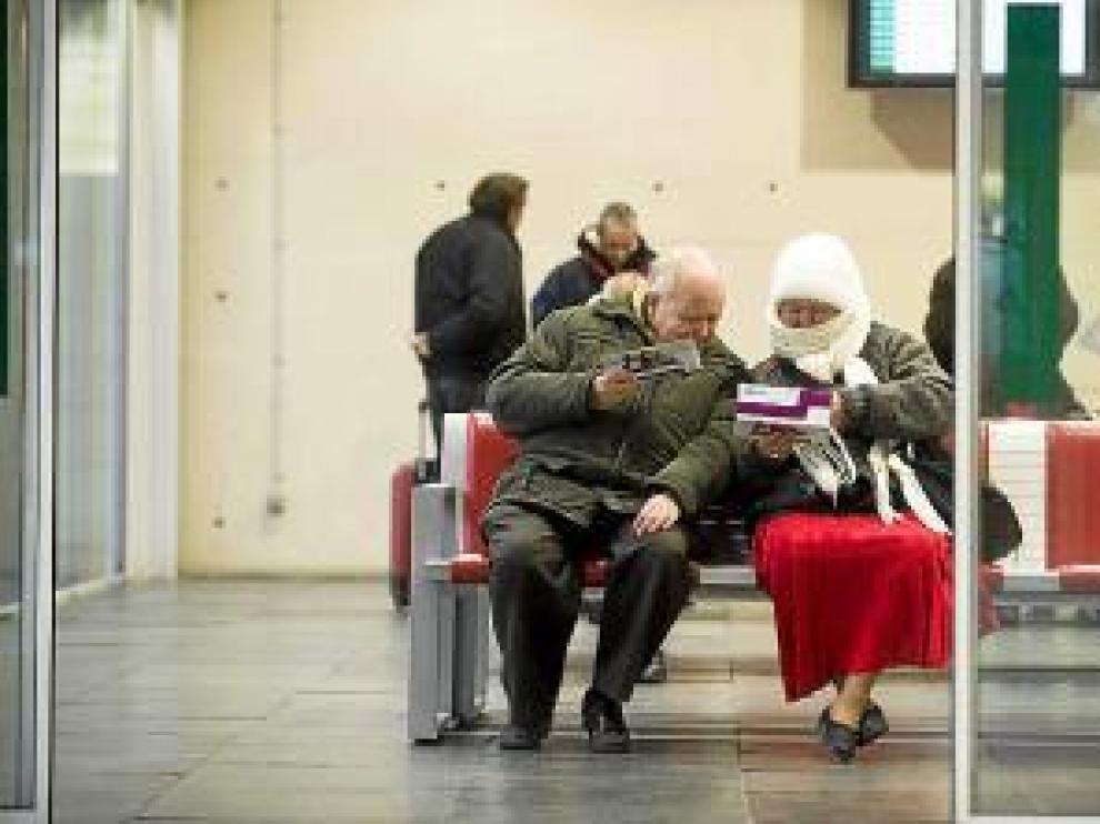 Dos pasajeros esperan abrigados en la estación de Delicias.