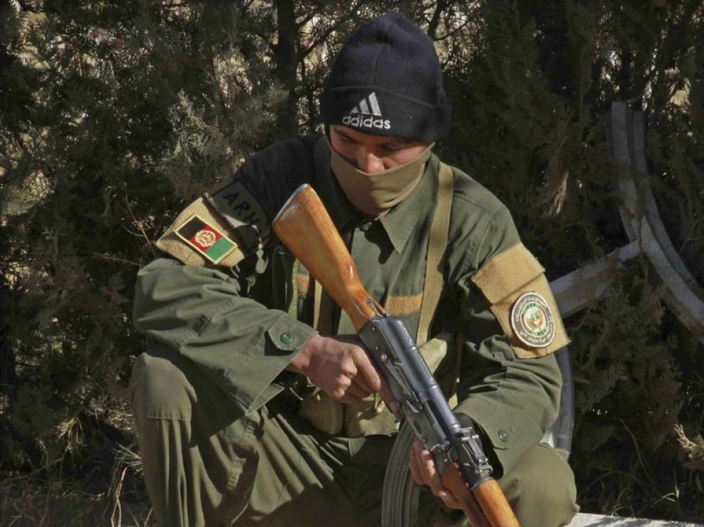 Un agente de seguridad afgano inspecciona munición y detonadores.