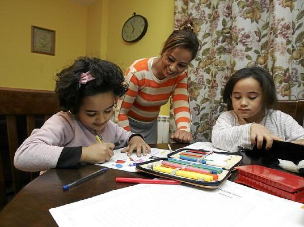 Amina y Sofía hacían ayer sus deberes con su madre Jamila, en su casa de Santa Cilia.