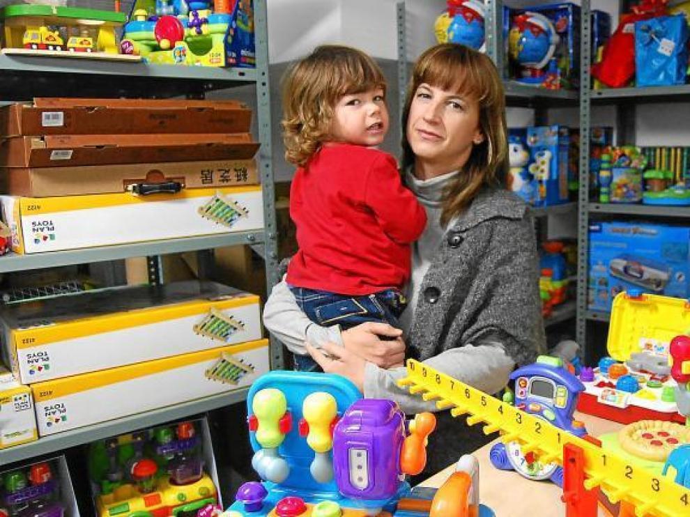 Magda, con su hijo pequeño en brazos, y rodeada de los cientos de juguetes que ofrece a través de su empresa de alquiler.