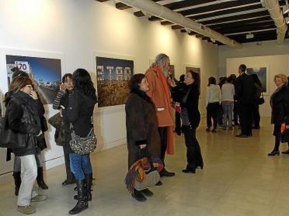 Varias personas contemplan la exposición en la inauguración.