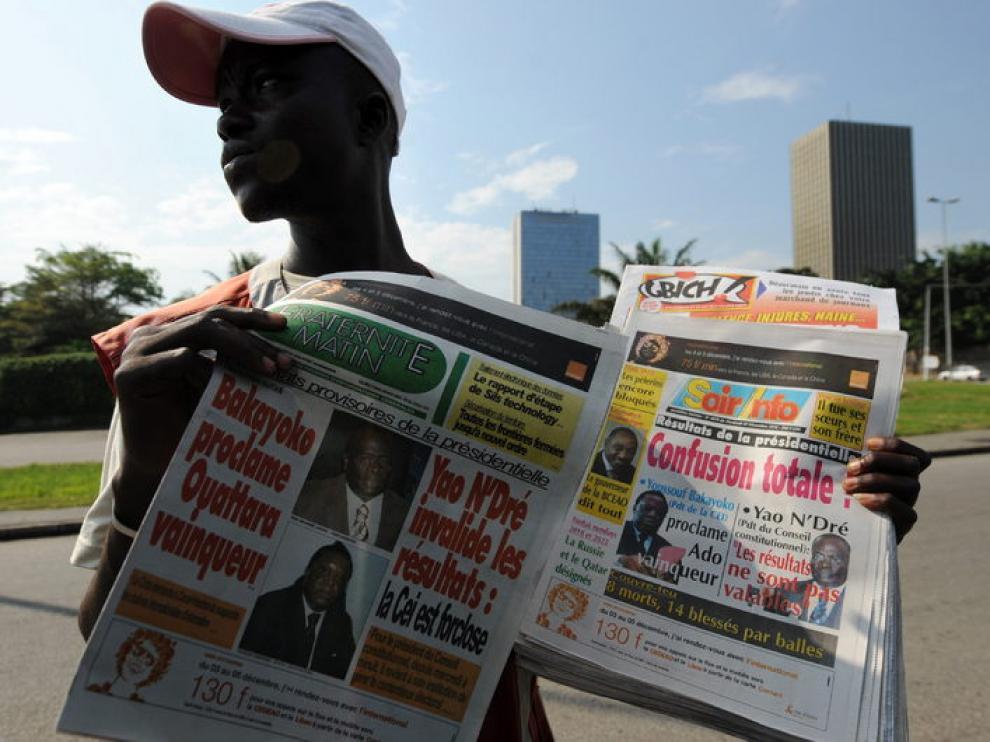 Un joven sostiene los periódicos del día, que expresan la confusión reinante en el país.