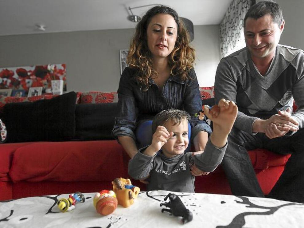 Javier coge un muñeco con su nueva mano bajo la atenta mirada de sus padres, Alicia Orce y Rubén Gimeno.