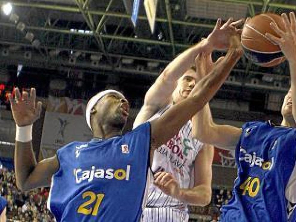 Barac intenta hacerse con el balón ante dos jugadores del Cajasol.