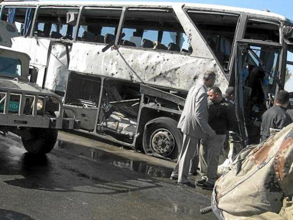 Iraquíes inspeccionan los restos de un autobús objetivo de un atentado en Bagdad, el sábado.