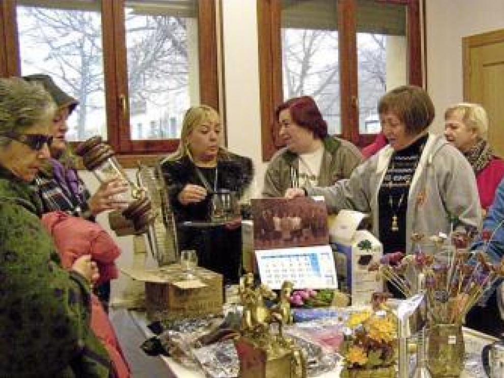 Varias mujeres ojean los objetos a la venta en el rastrillo.