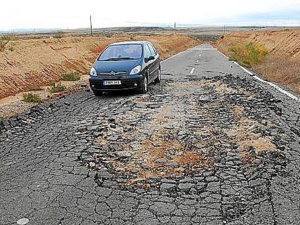 Un turismo trata de sortear un gran socavón que ocupa casi todo el ancho de la carretera.