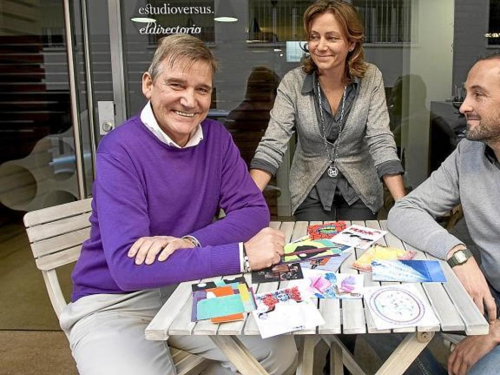 Javier Almalé y Nieves Añaños, del Estudio Versus, miran a José Carlos Aguelo, con algunas de las postales como testigo.