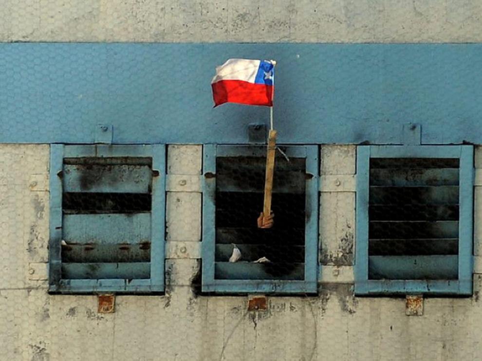Un interno muestra una bandera chilena desde el interior de la cárcel.