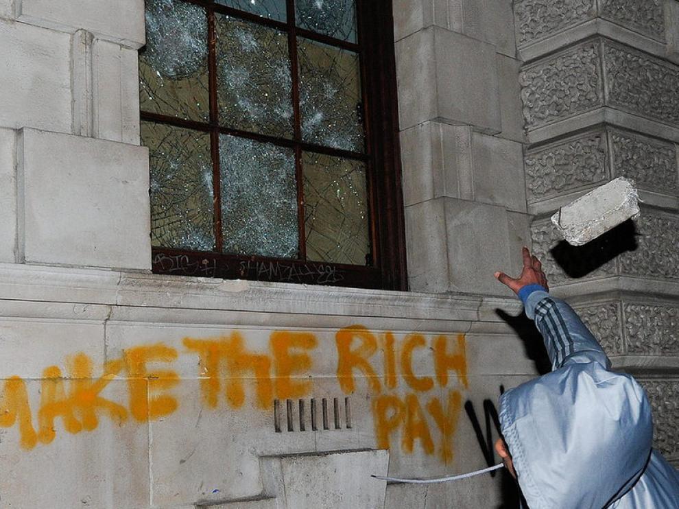 Un joven destroza la ventana de un edificio.