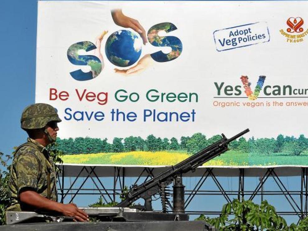 Un militar pasa delante de un cartel que insta a salvar el planeta, ayer, en Cancún.