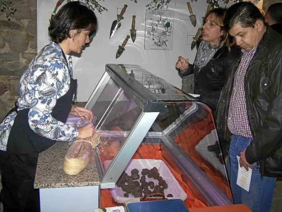 Dos compradores se interesan por las trufas en un mostrador del mercado de Graus.