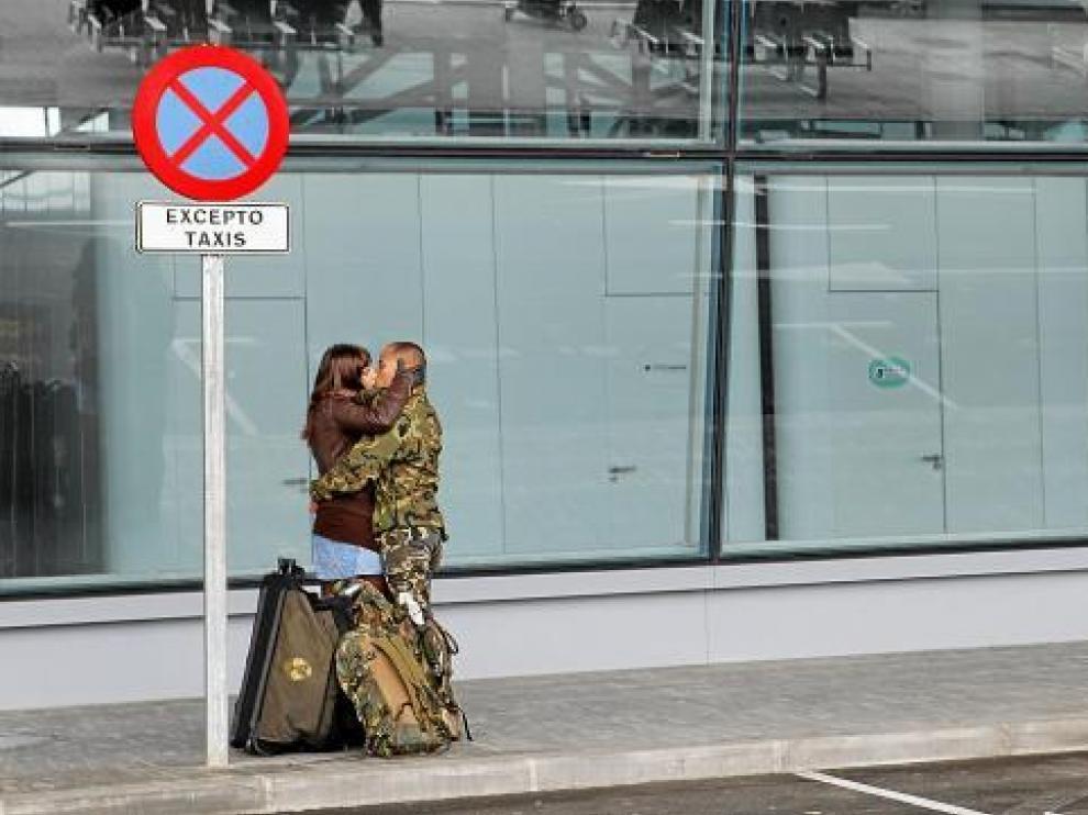 Un militar de la Brigada de Caballería Castillejos II besa a su pareja, ayer, en el aeropuerto de Zaragoza.