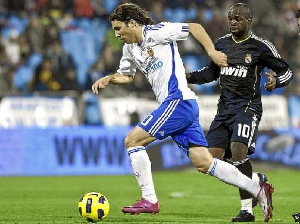 Bertolo avanza con el balón, perseguido por Arbeloa y Lass.