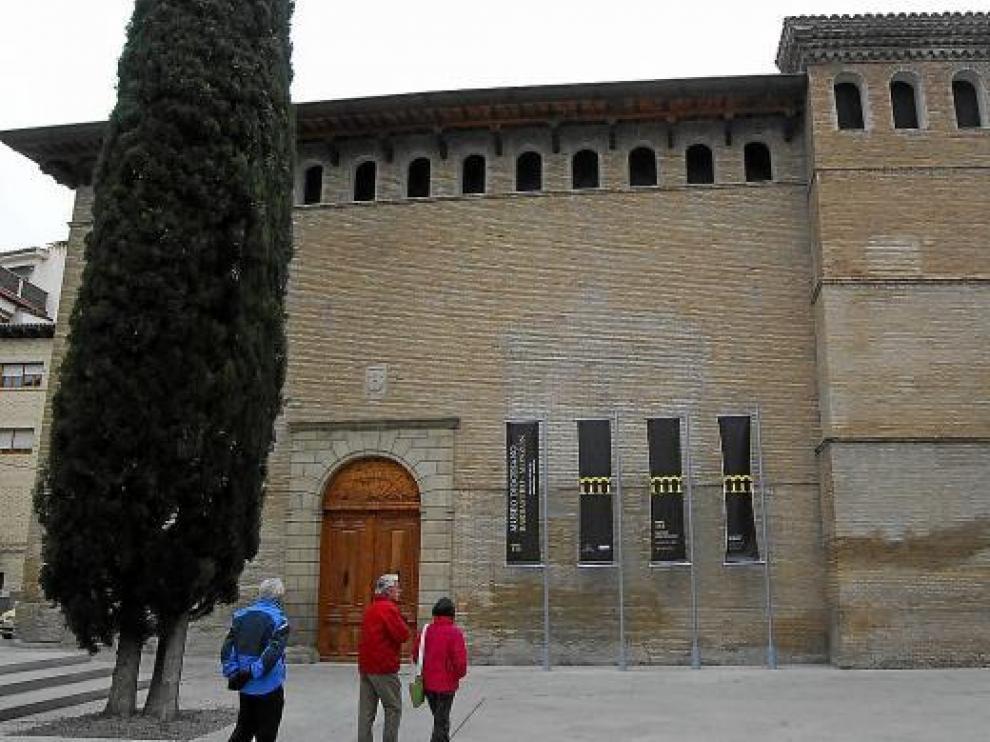 Varias personas pasan junto al museo, que conserva el aspecto exterior de estilo gótico aragonés.