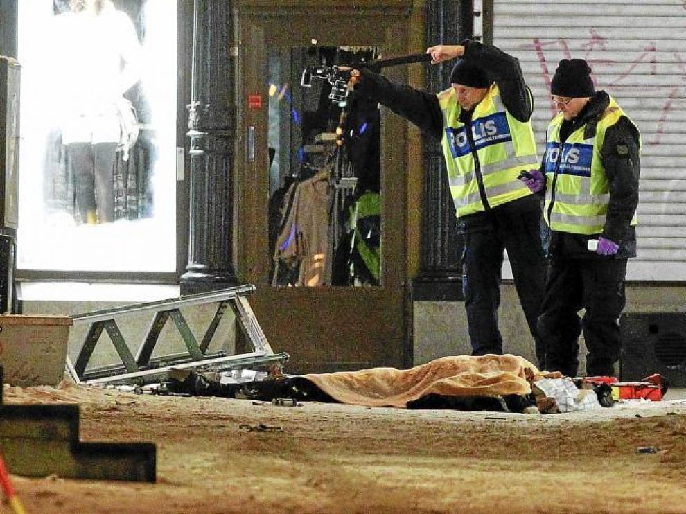 Policías forenses examinan los restos del supuesto suicida que el sábado hizo estallar una bolsa que contenía bombas.