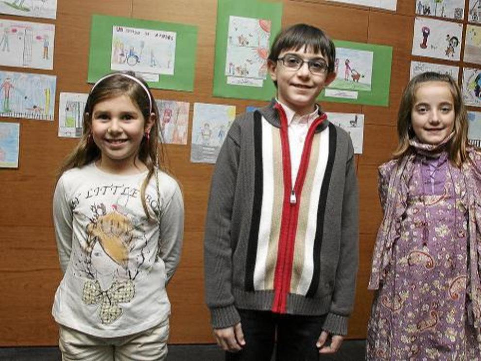Los tres niños premiados posan delante de sus dibujos, con los que ilustran la igualdad.