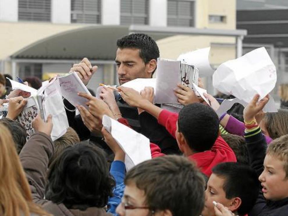 Roberto García firma autógrafos entre una nube de niños.