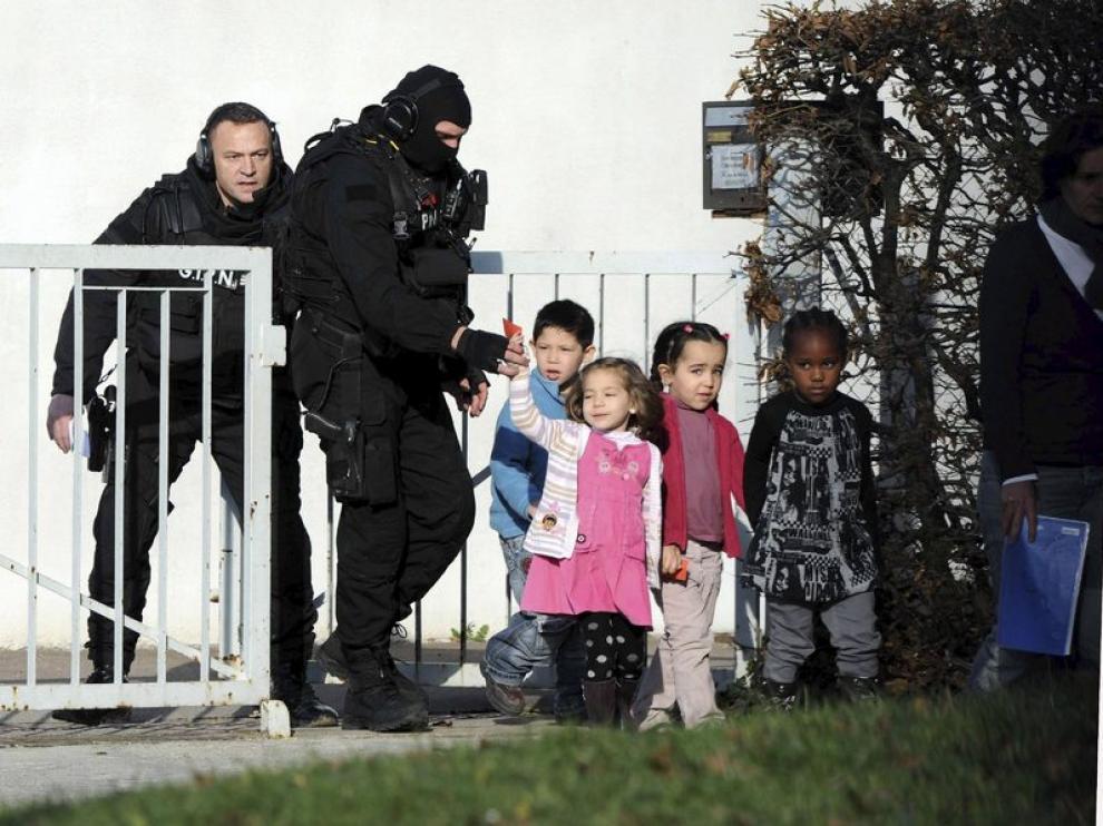 Policías acompañan a varios niños de un colegio de Besançon, en Francia, donde acabó felizmente el secuestro de una clase