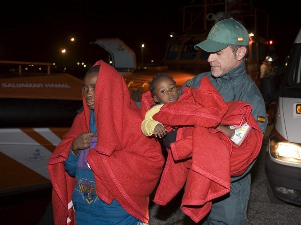 Un miembro de la Guardia Civil ayuda a dos de los treinta inmigrantes.