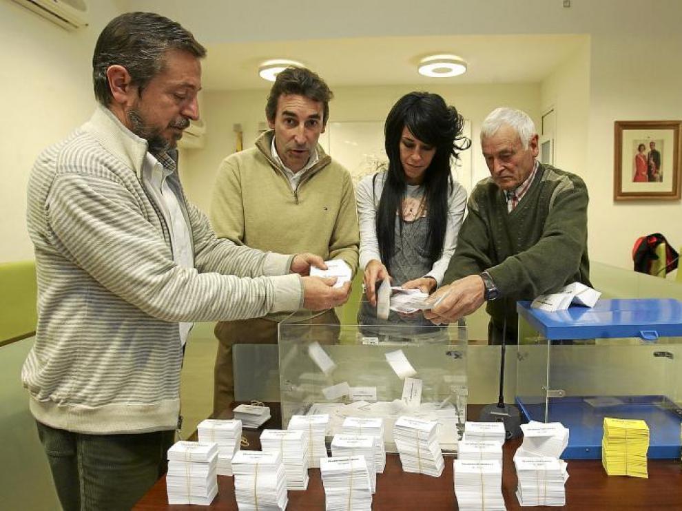 Momento de la introducción de las papeletas con los números en las urnas preparadas para el sorteo.