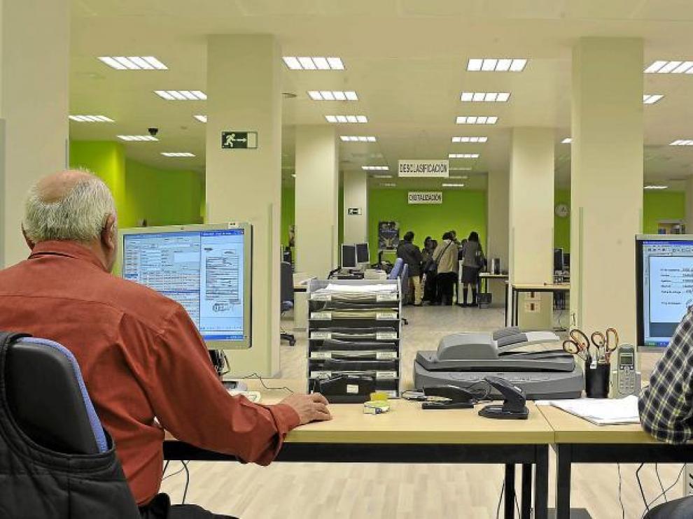 Ángel Nadal y Carlos Mateo (los dos de espaldas) son dos de los trabajadores del centro de digitalización del Grupo DFA en Zaragoza.