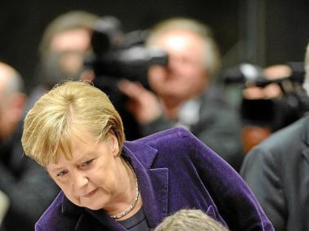 La canciller Angela Merkel se acerca a Zapatero, ayer.